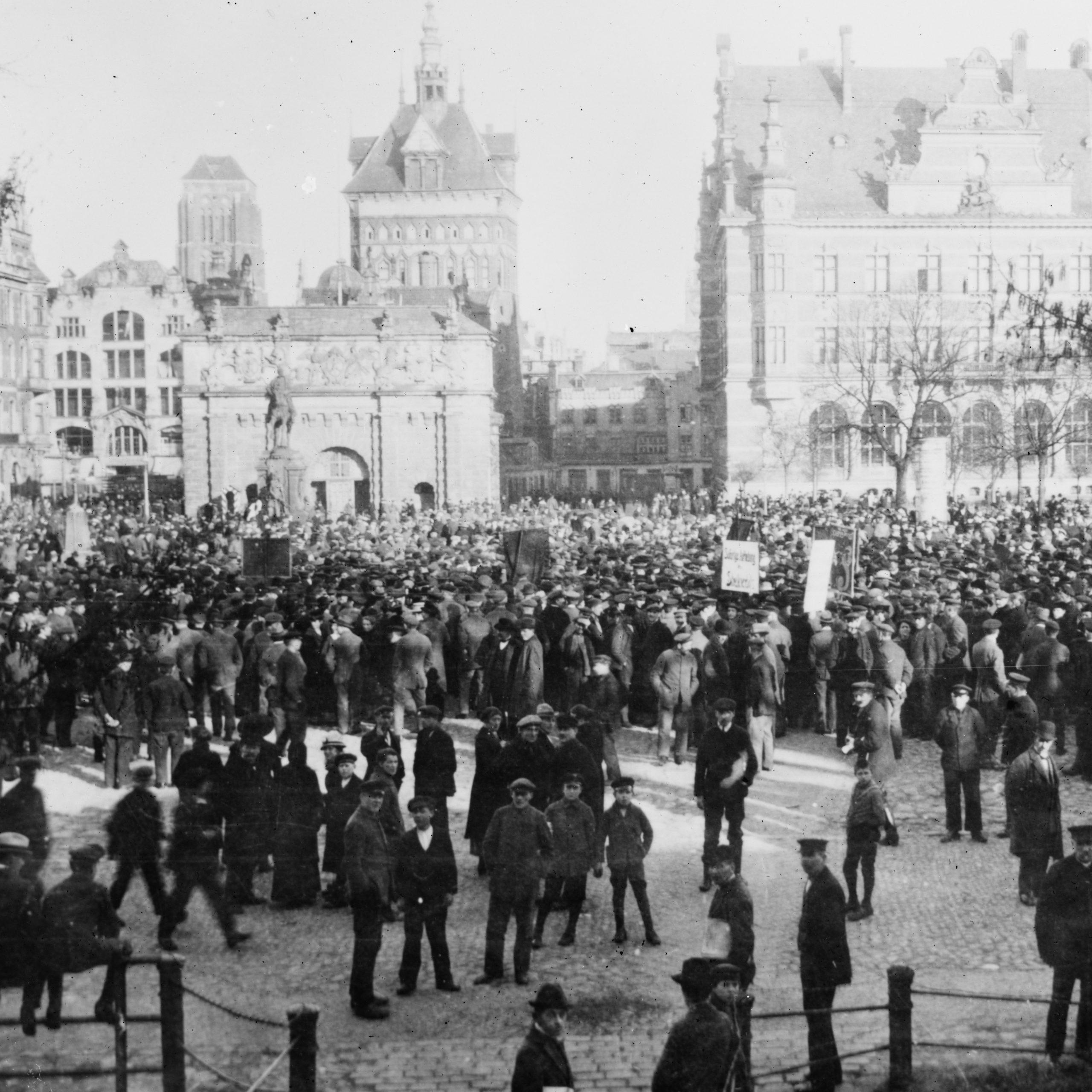 tłum ludzi przed bramą wyżynną i budynkiem banku w Gdańsku