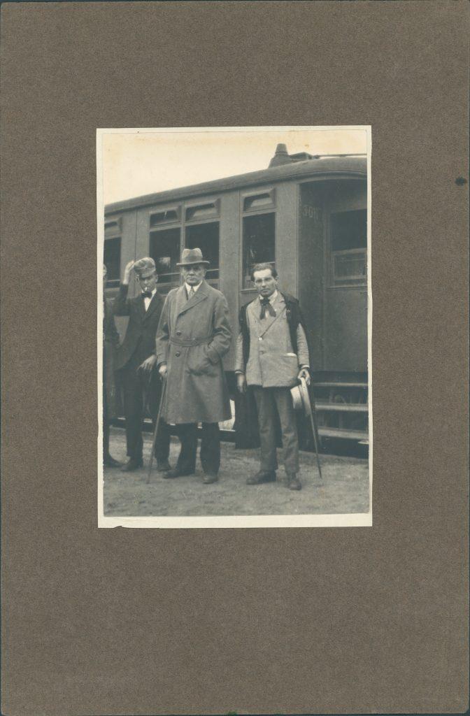 3 mężczyzn przed wagonem kolejowym
