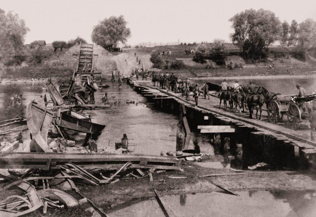 tymczasowy drewniany most, po którym idą konie i wozy, obok zrujnowanego mostu w rzece