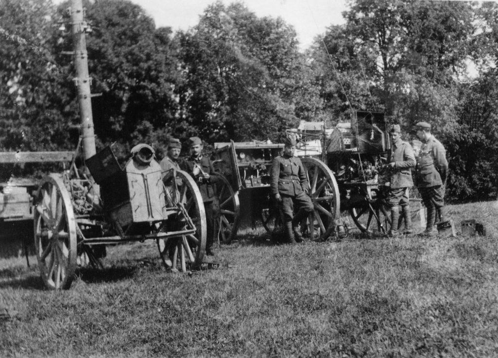 żołnierze przy wozach polowych z elelmentami radiostacji