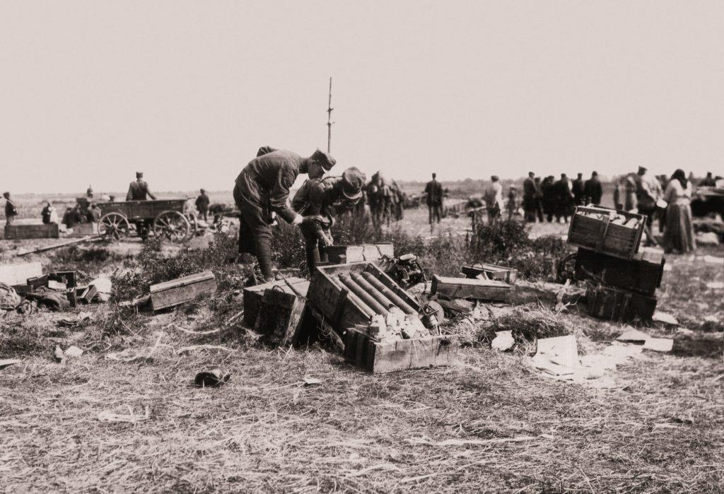 polscy żołnierze pochylający się nad skrzynkami z amunicją w polu