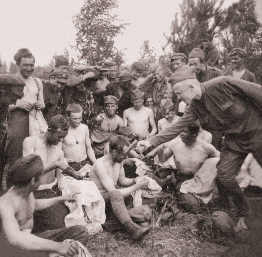 żołnierze uśmiechnięci i półnadzy podczas odpoczynku jeden z nich celuje w kolegę z pistoletu