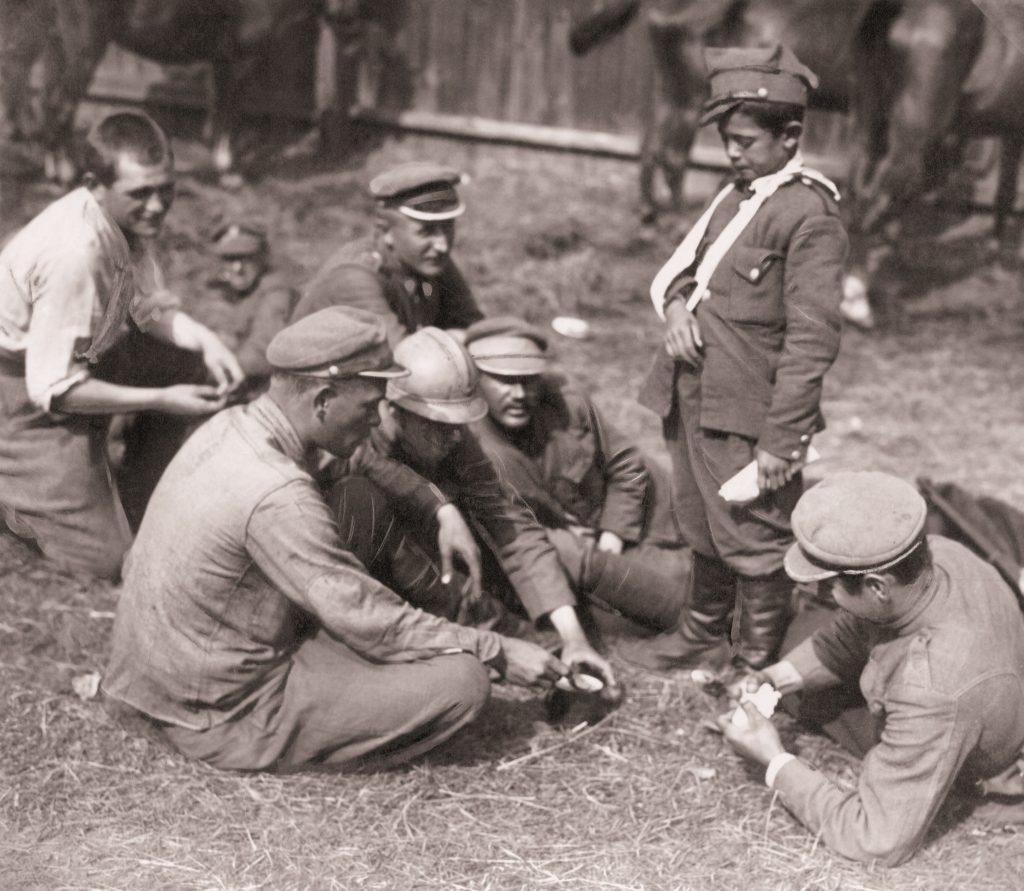 grupa żołnieży jedzących z jednej menażki, przy nich stoi chłopczyk z ręką na temblaku