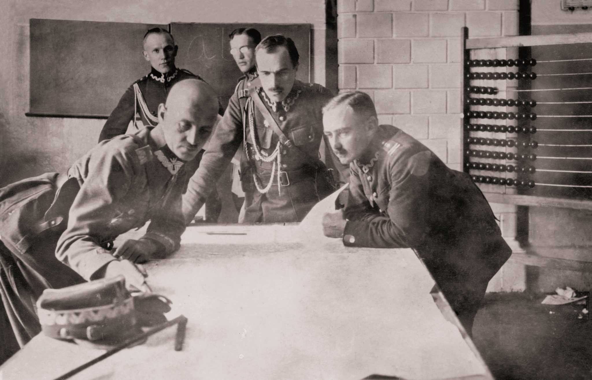 trzech mężczyzn pochylionych nad mapą na stole