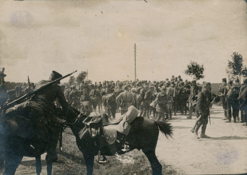 ludzie opuszczający tłumnie miasto, na pierwszym planie osiodłany koń