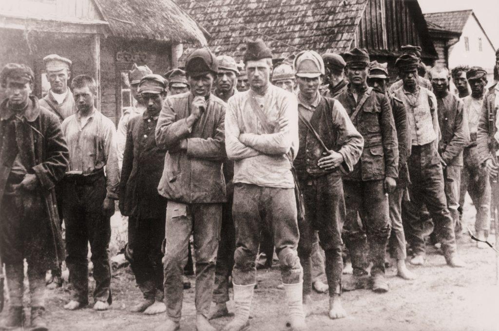 grupa ężczyzn w obdartych ubraniach przed chatami