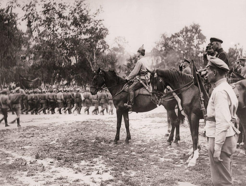 mężczyzni na koniach obserwujący przechodzące wojska w kolumnach