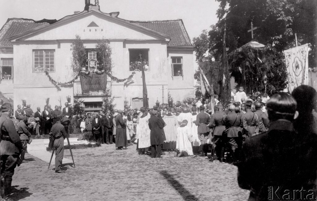 udekorowany patriotycznie dworek, pod nim procesja z krzyżem dookoła żołnierze w modlitwie