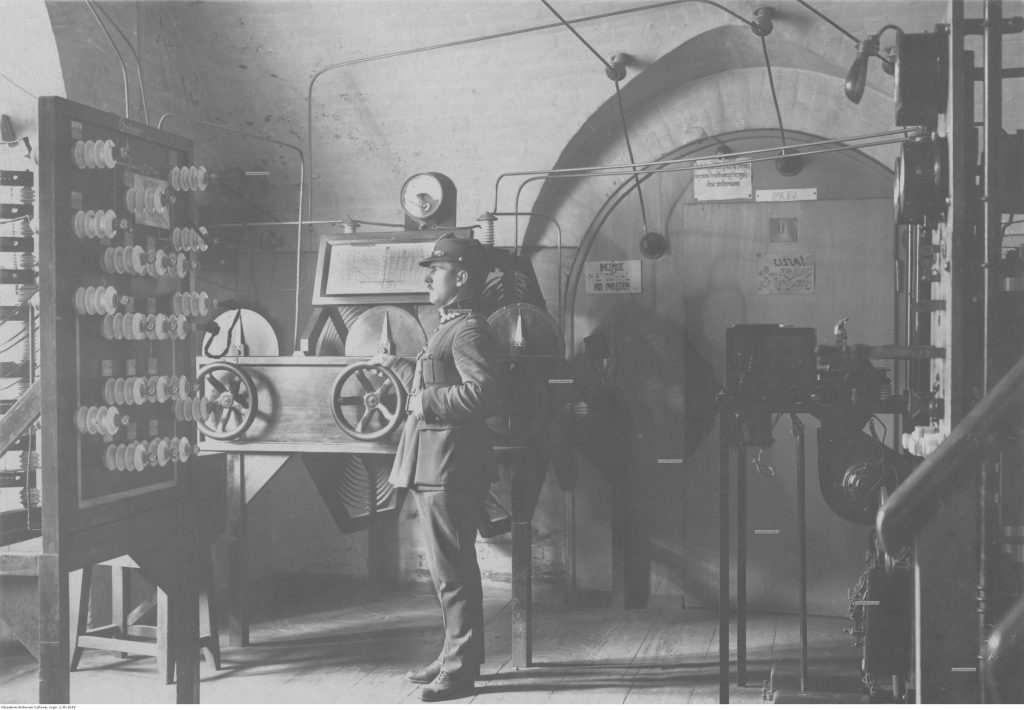 pokój wypełniony maszynami, na środku stoi żołnierz