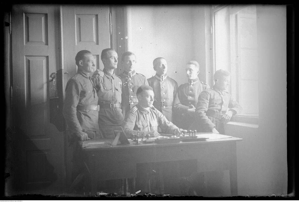 Grupa wojskowych w wnętrzu budynku.