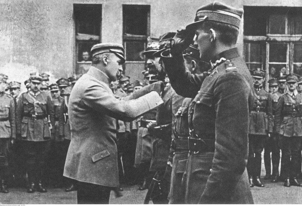 Naczelnik Państwa Józef Piłsudski odznacza oficerów, w tle widzowie żołnierze