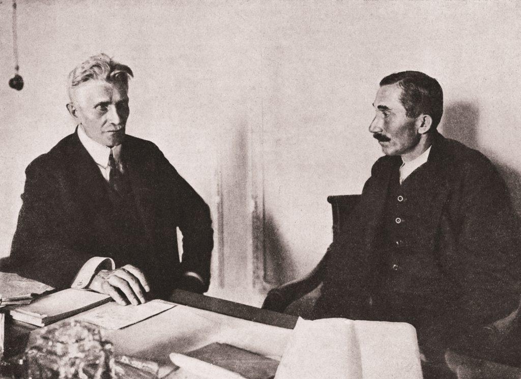 dwóch meżczyzn przy stole z dokumentami