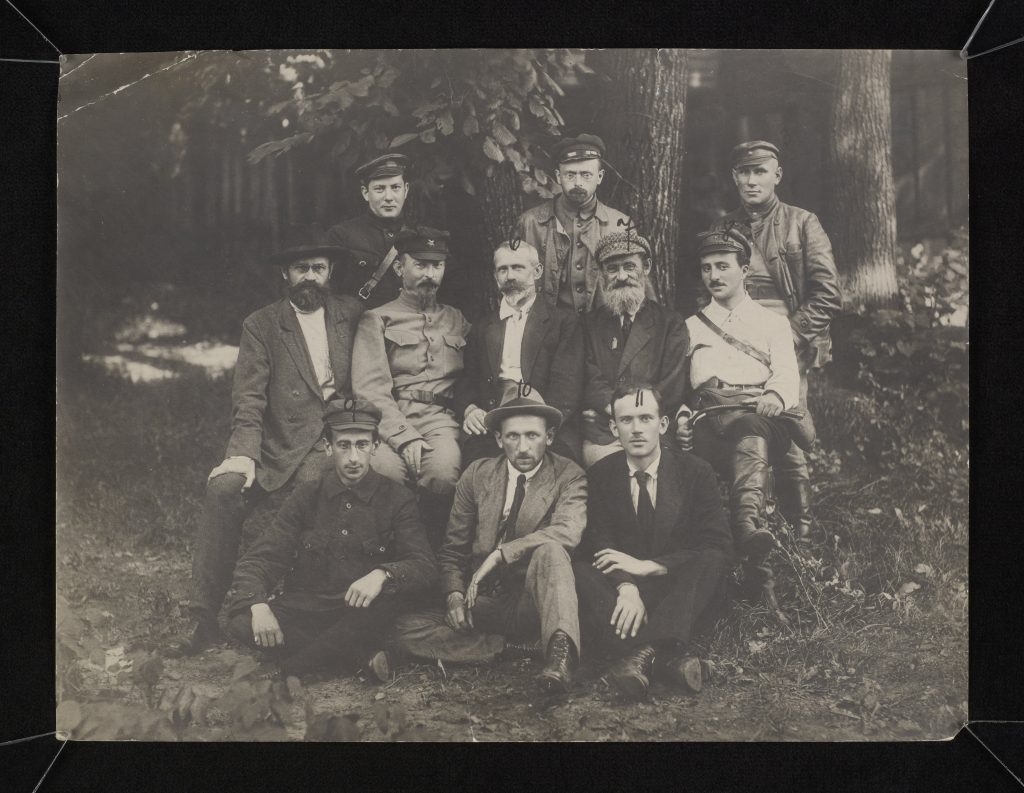 grupa ludzi pozująca do zdjęcia grupowego w lesie