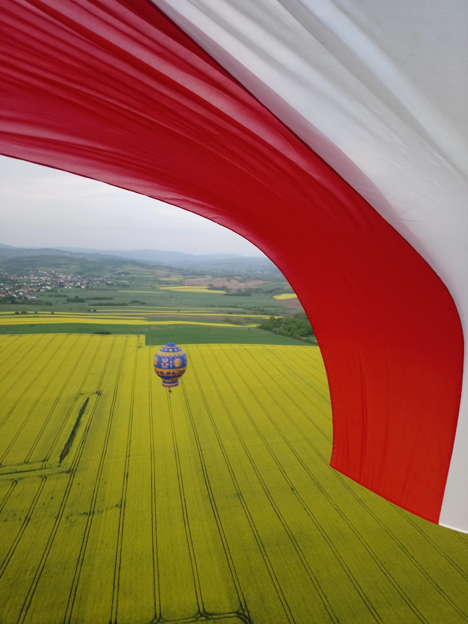 zdjęcie z lotu ptaka przedstawia balon lecący nad polami, w rogu powiewająca polska flaga