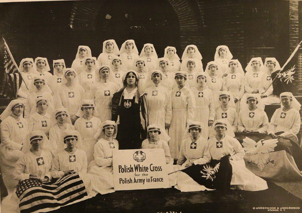 zdjcie grupowe kobiet, większość ubrana na biało, w środku na czarko Helena Paderewska. Sanitariuszki trzymają transparent z napisem po angielsku