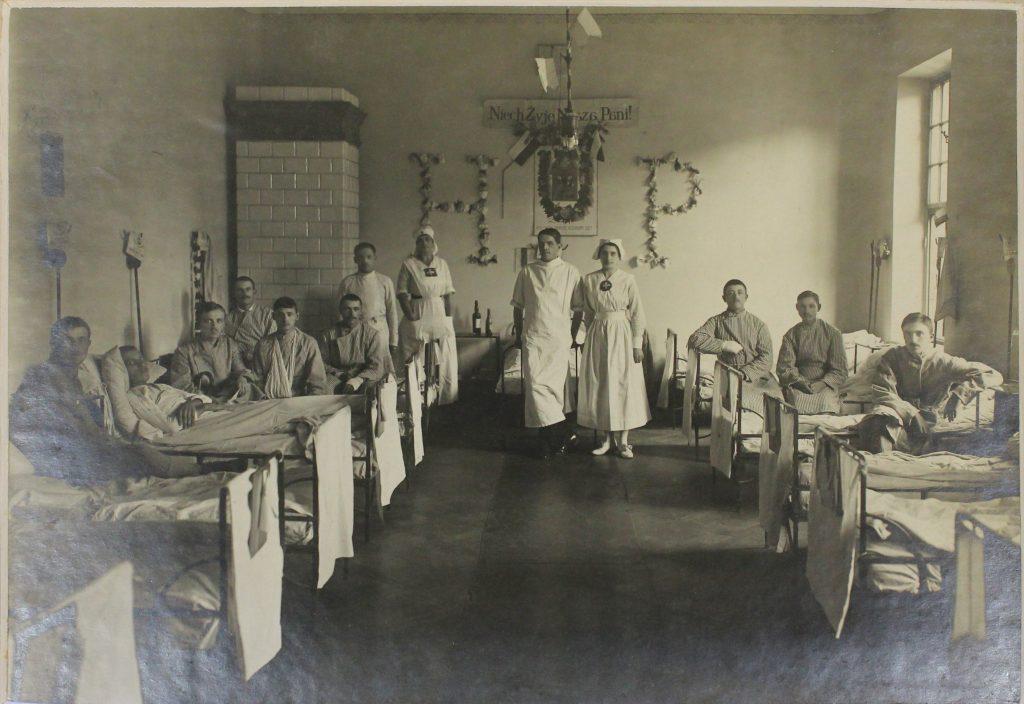 sala szpitalna, na łóżkach pod ścianami siedzą ranni mężczyźni, w centrum stoją 2 sanitariuszki z lekarzem, w tle na ścianie z kwiatów litery H i P