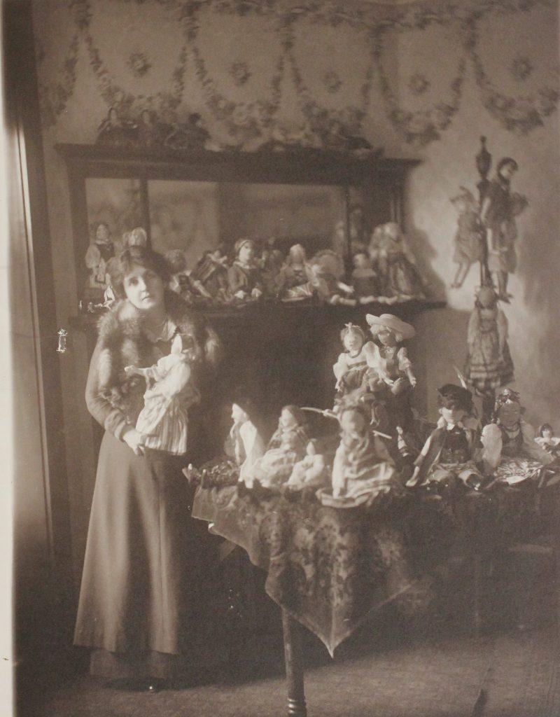 Kobieta w sukni w uksusowym wnętrzu, na stole przed nią i na kredensie za nią poukładane rzesze lalek