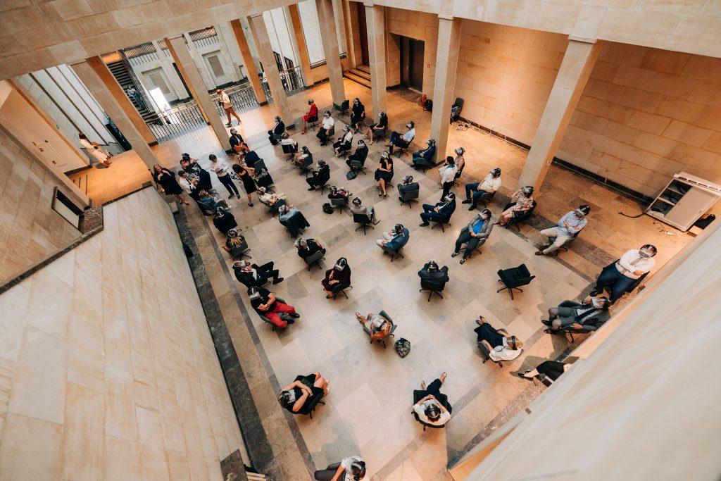 w sali wyłożonej marmurem ludzie sziedzą na brotowych krzesłach w równych odtępach z googlami VR na oczach