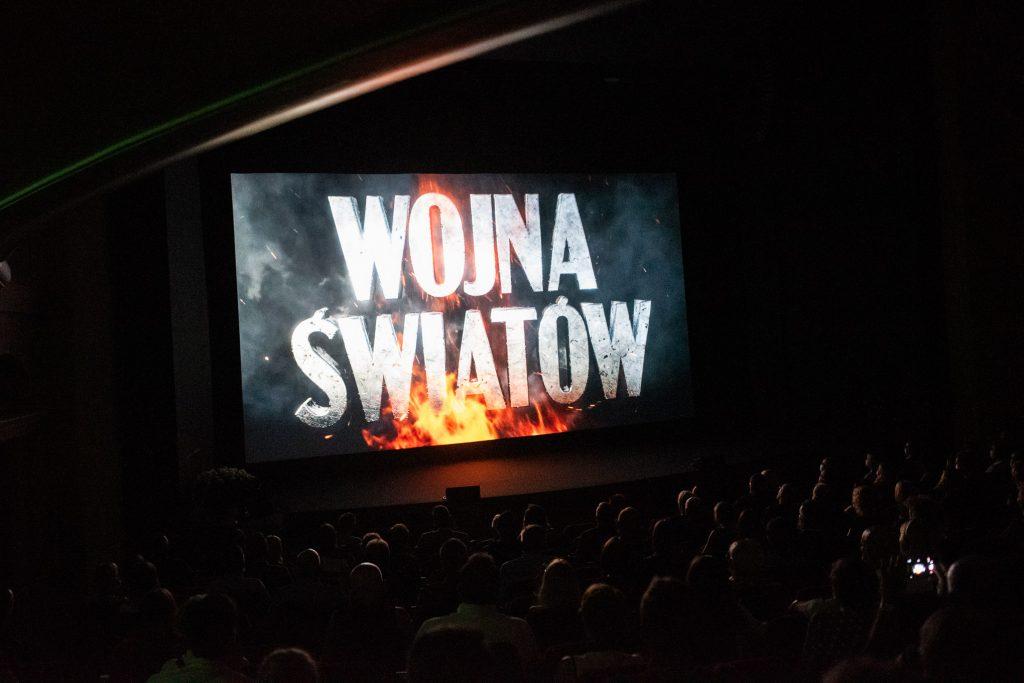 na scenie wyświetlany film z planszą tutułową, rozbłyski na konturacj sylwetek na widowni