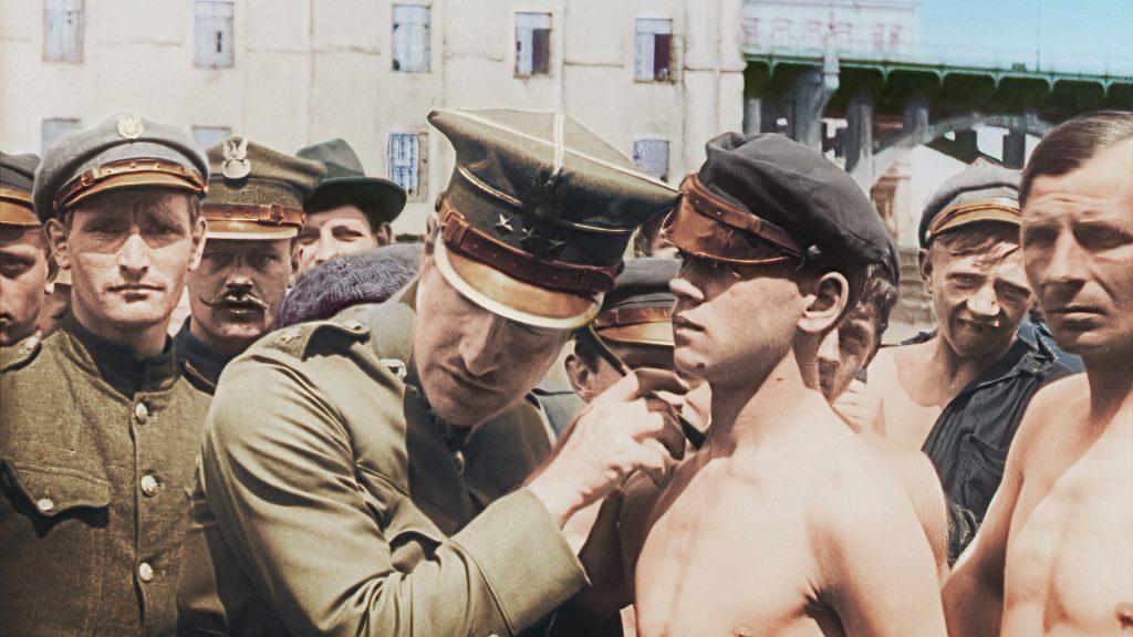 tłum ludzi, na pierwszym planie mężczyzna w mundurze trąkną osłuchuje półnagiego młodzieńca w czapce