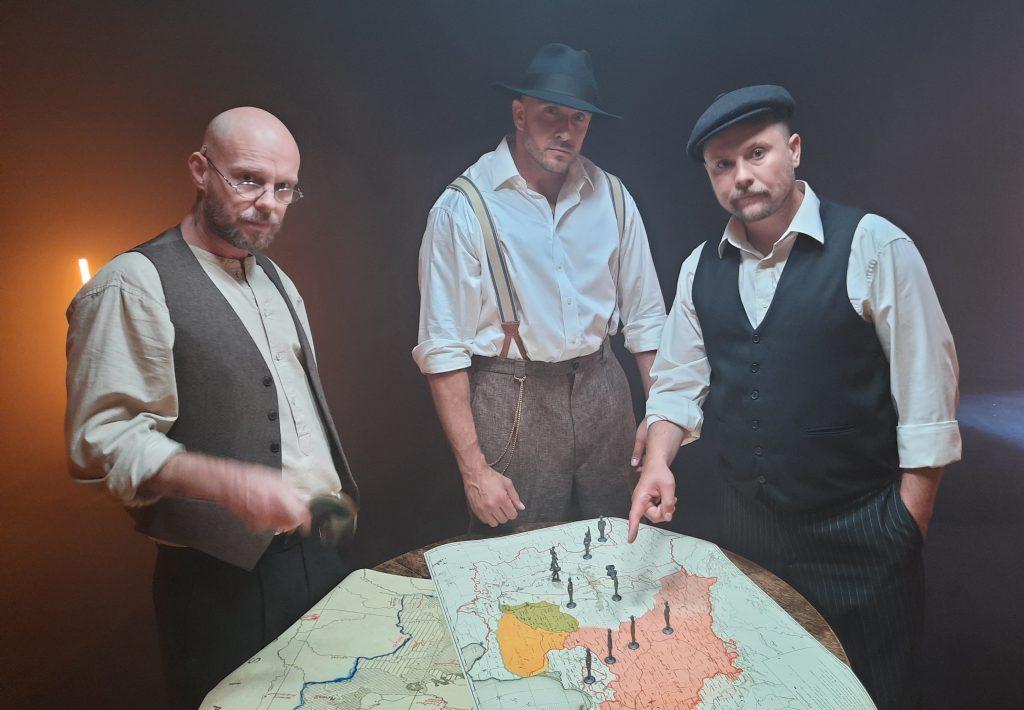 członkowie Zipery - Pono, Koras i Fu w strojach jak sprzed stu lat przed mapą