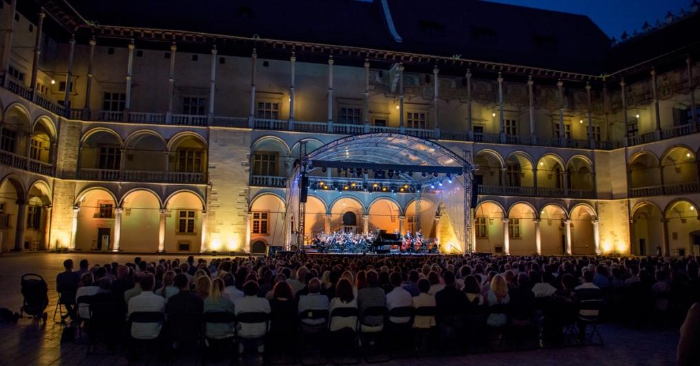"""zdjęcie przedstawia scenę, na której odbywa się koncert w ramach festiwalu """"Wawel o zmierzchu"""". Przed sceną na krzesłach siedzi publiczność"""