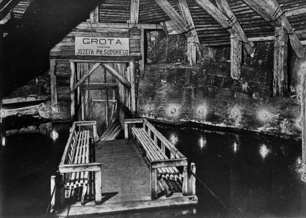podziemna grota zalana zodą, na wodzie prom z ławeczkami, nad wejściem do groty napis Grota im. Józefa Piłsudskiego