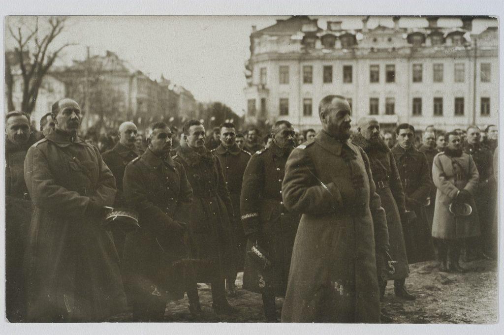 mężczyźni w płaszczach stojący na placu, w tle budynki miejskie