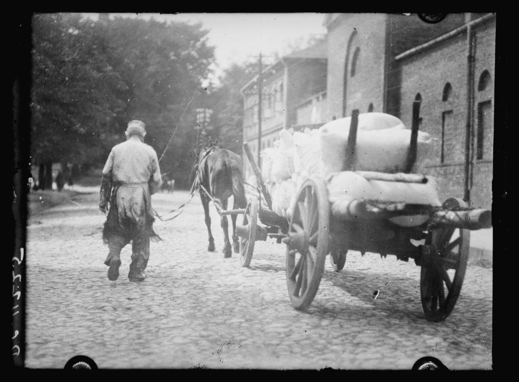 na ulicy jadący wóz konny od tyłu z workiem mąki, obok człowiek