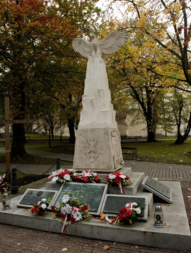 widok na pomnik złożony z elementów dwóch pomników - cokołu z pierwszego, i częśći artystycznej z orłem z drugiego. Wokół, u stóp różne tablice i złożone kwiaty