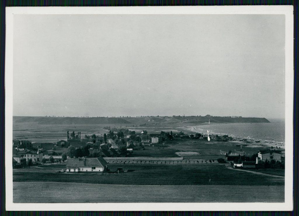 widok na płaski teren z radkimi zabudowaniami i morze
