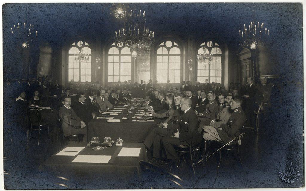 ozdobna sala wypełniona stołami z mężczyznami w garniturach prowadzącymi rokowania