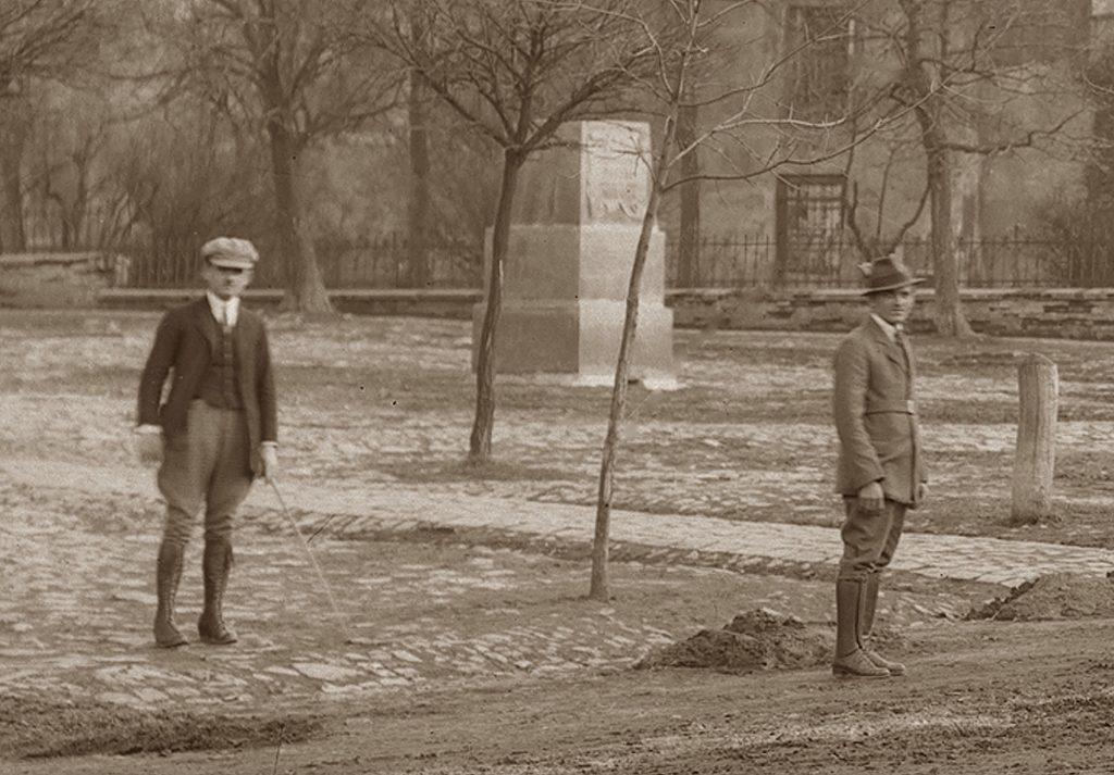 dwaj mężczyźni stojący w parku z młodymi drzewami, za nimi bryła pomnika