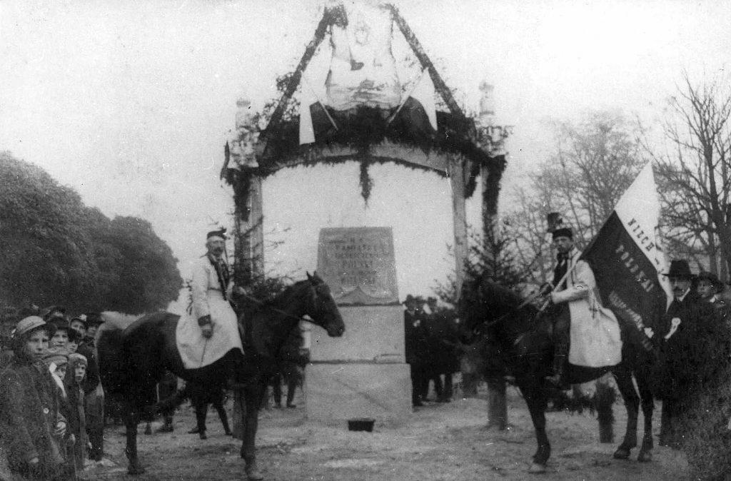 pomnik pod odświętną bramą, obok stoją ułani na koniach