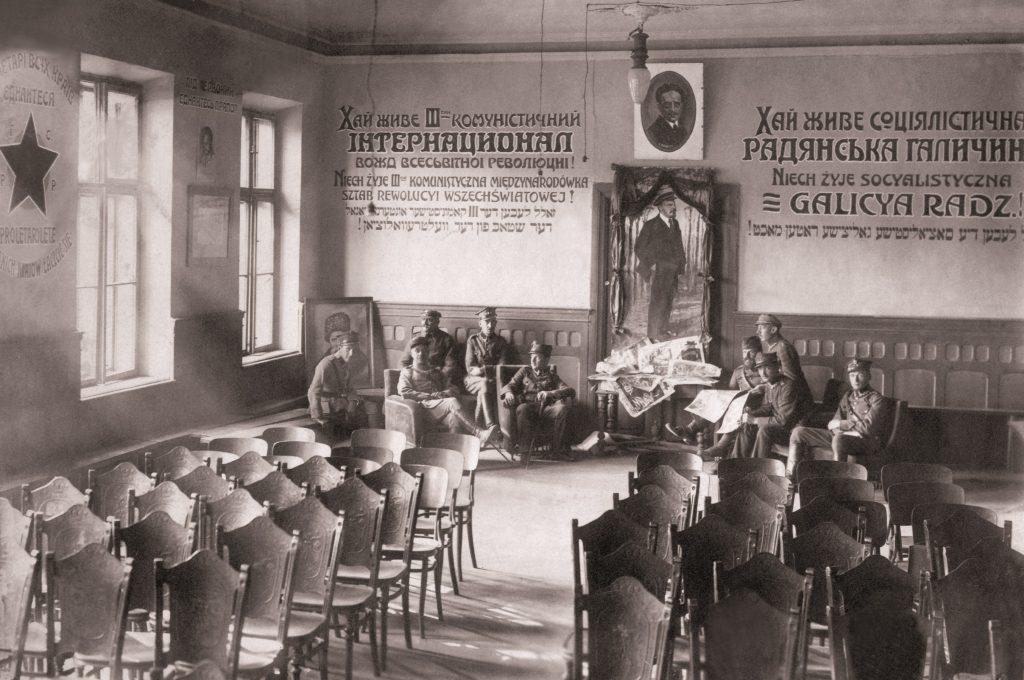 klasa z krzesłami, na ścianach napisy cyrylicą i ozdobione portrety, pod nimi pozuje kilku żołnierzy