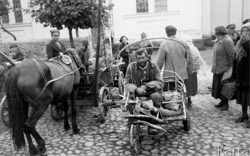 okaleczony mżczyzna siedzący na wózku okbok koń i ludzie