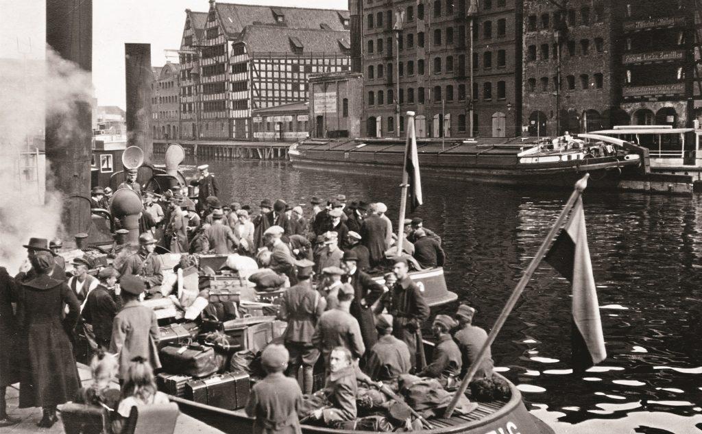 ludzie na łódce na rzece, w tle spichrze gdańskie