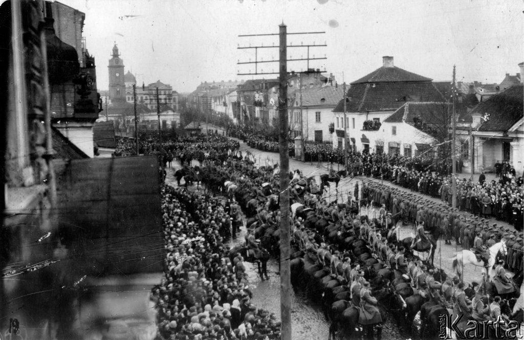 równe kolumny żołnierskie odące ulicą, na chodnikach gapie, w tle budynki