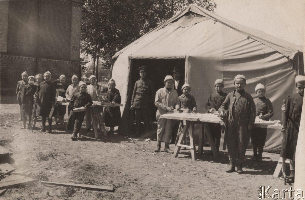 namiot, przed nim stoły z ludźmi zgromadzonymi wokół nich
