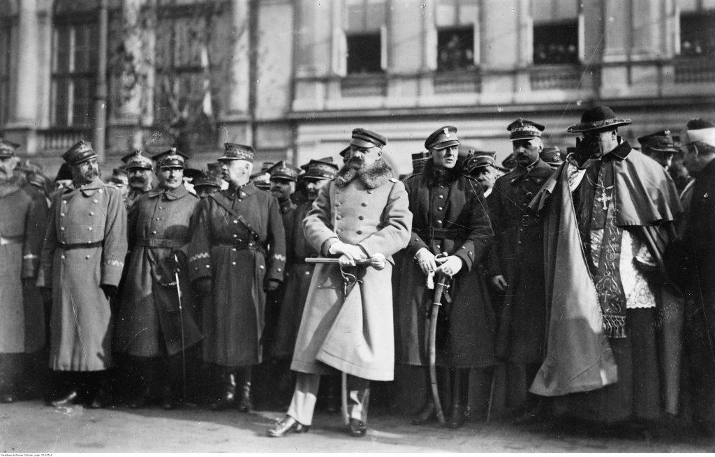 grupa oficjeli w płaszczach, na pierwszym planie w jasnym okryciu piłsudski z buławą