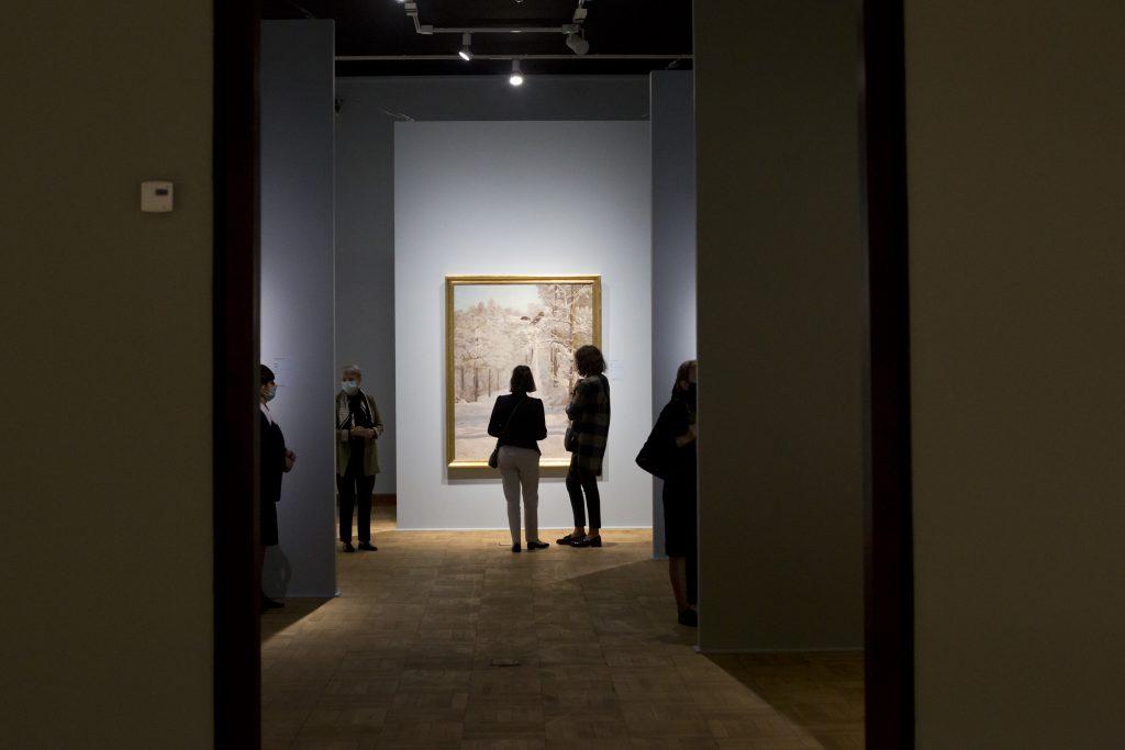 sala wystawowa z rozproszoymi ludźmi oglądającymi obrazy