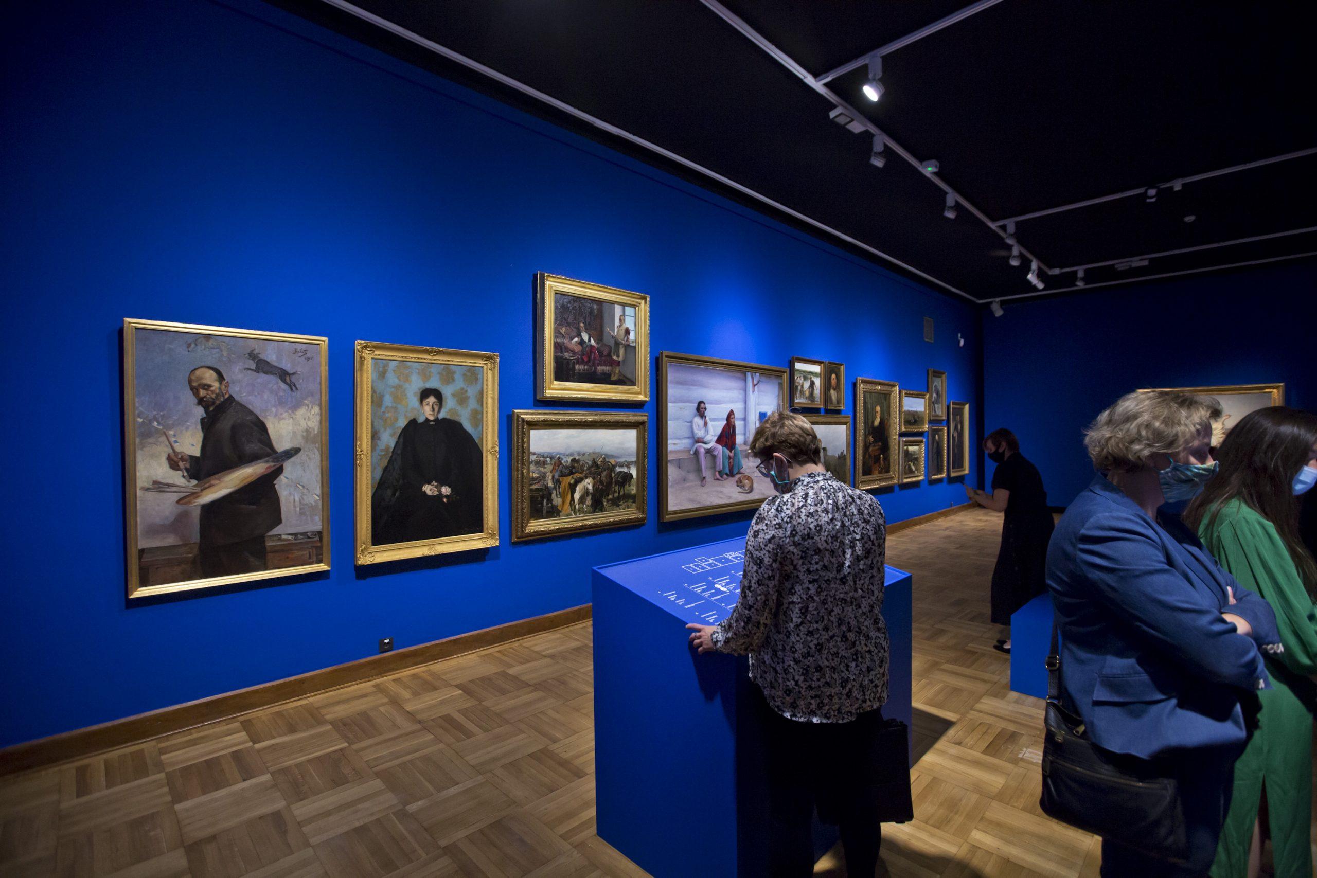ściana z zawieszonymi obrazami, na pierwszym planie kobieta przy ekspozytorze
