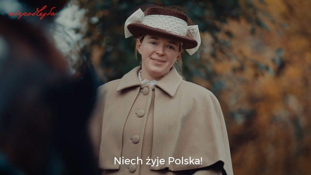 kobieta na powozie w retro ubraniu patrzy w dół z uśmiechem po wypowiedzeniu kwestii niech żyje polska