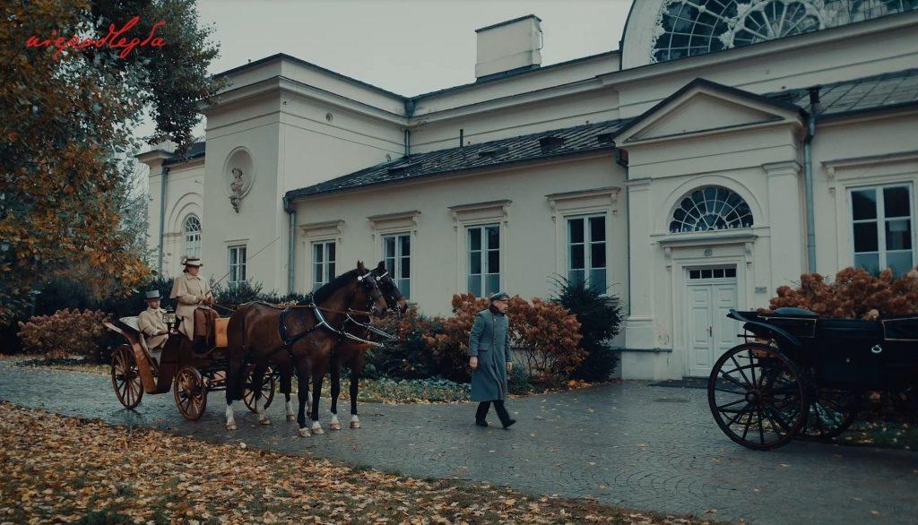 przed eleganskim budynkiem zaparkowane są dwa powozy, Piłsudski idzie do wejścia