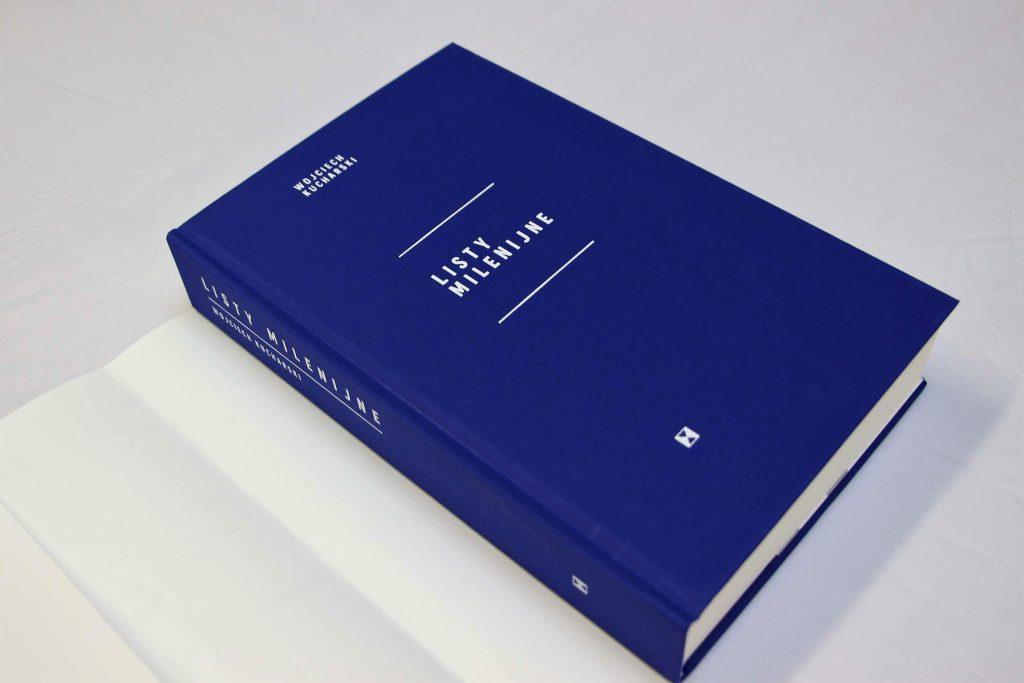 """Fotografia przedstawia granatową okładkę książki zatytułowanej """"Listy Milenijne"""" autorstwa Wojciecha Kucharskiego. W tle znajduje się biała obwoluta książki"""
