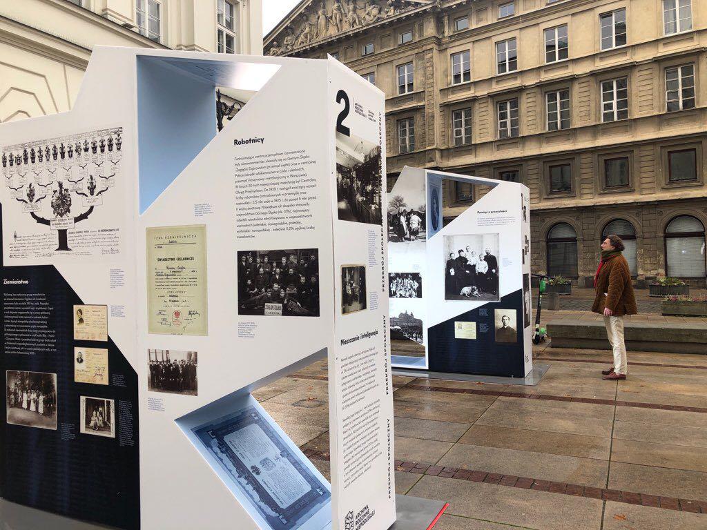 ekspozytory wystawy obok pomnika, na ulicy
