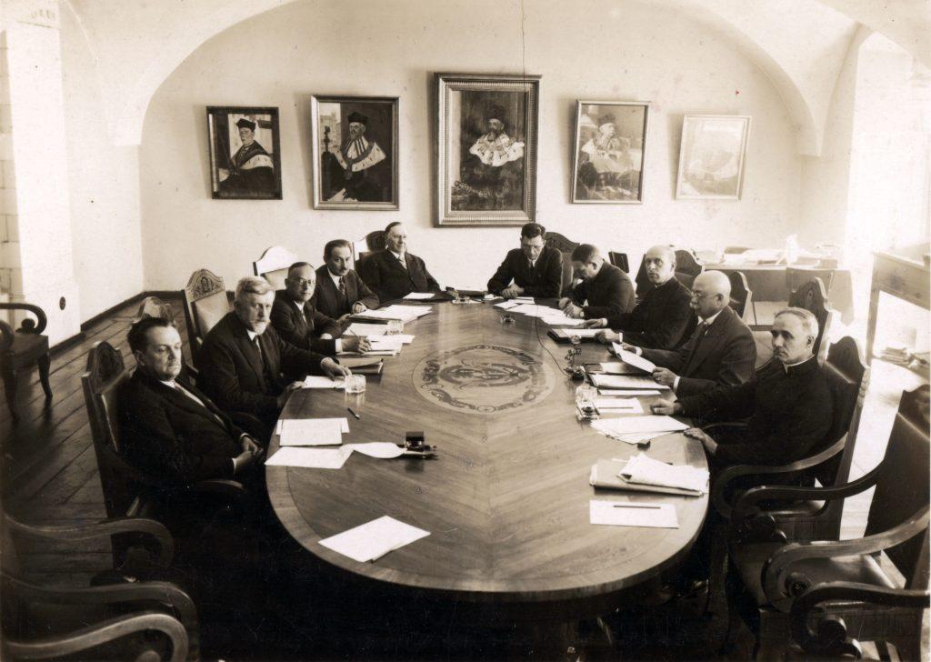 elegancko ubrani mężczyźni siedzący wokół eliptycznego stołu, na ścianie portrety rektorów