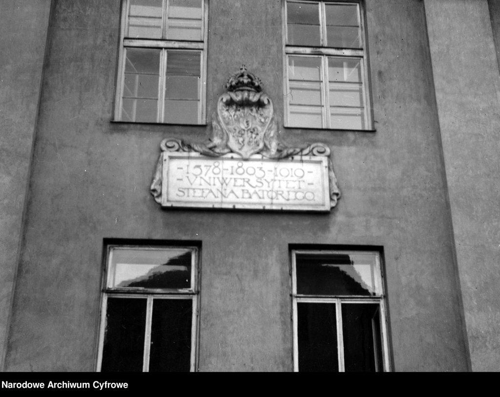 na budynku umieszczone godło uniwersyteckie z tablicą z napisem poniżej
