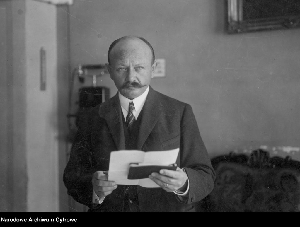 mężczyzna z dokumentami w dłoni w gabinecie naukowym, w tle np. widoczny telefon. Zdjęcie czarno-białe.