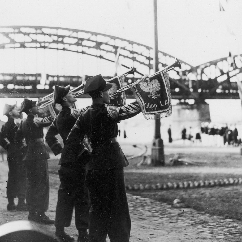 żołnierze w mundurach na brzegu rzeki dmący w trąbki, w tle mosty